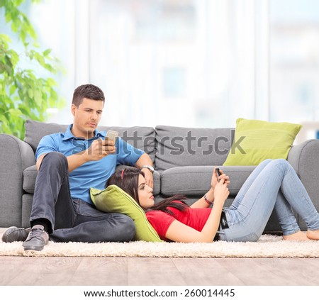 Young couple surfing on their cell phones seated by a sofa at home shot with tilt and shift lens - stock photo