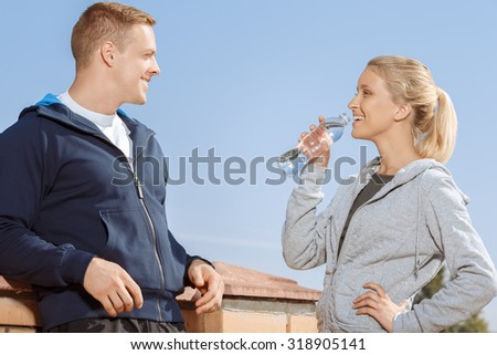 Young couple taking a break from exercise outdoors - stock photo