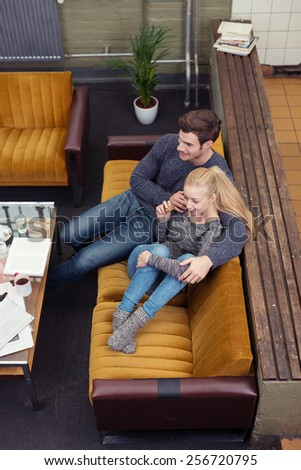 Young couple taking a break from paperwork as they relax on the sofa together in their living room, high angle view - stock photo