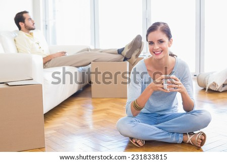Young couple taking a break from unpacking in their new home - stock photo