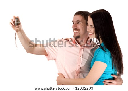 Young couple taking a photo of themselves (isolated on white) - stock photo