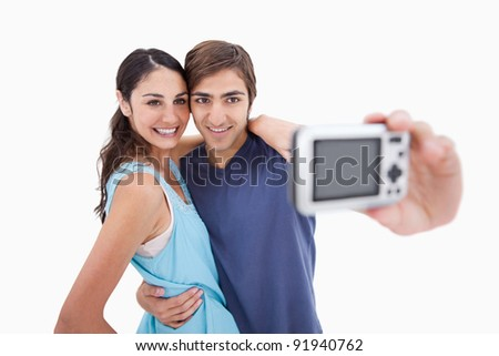 Young couple taking a picture of themselves against a white background - stock photo