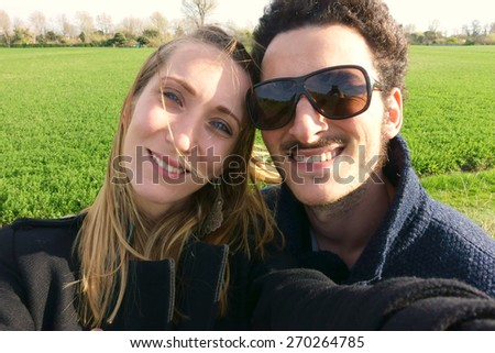 Young couple taking a selfie and smiling - stock photo