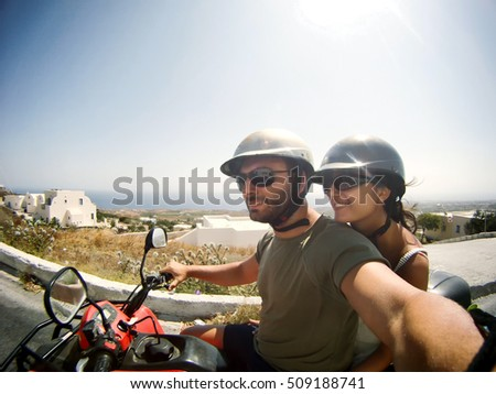 Young couple taking a Selfie by quad in Santorini Island