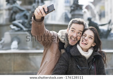 young couple taking a selfie of their grimaces - stock photo