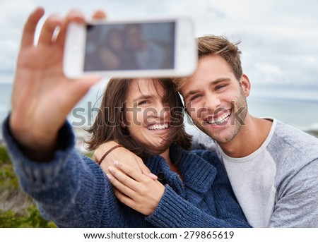 Young couple taking a selfie outdoors and looking happy and loving