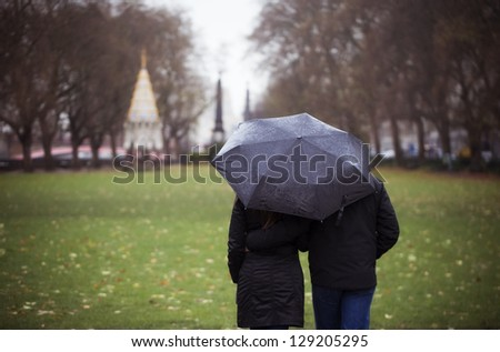 Young couple taking a walk in the park on a rainy day - stock photo