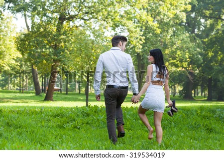 young couple taking a walk through the park