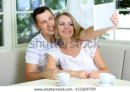 Young couple  taking  photo with tablet at home - stock photo