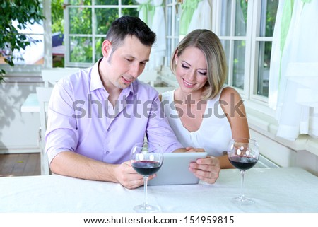 Young couple  taking photo with tablet in restaurant - stock photo