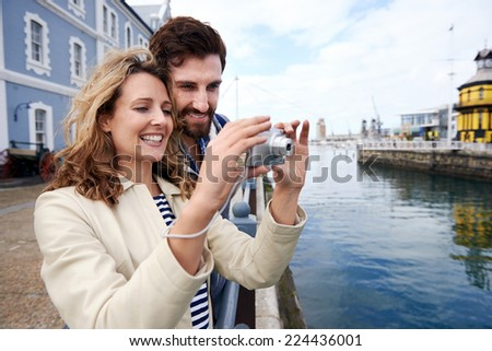 young couple taking photos on holiday as they travel together