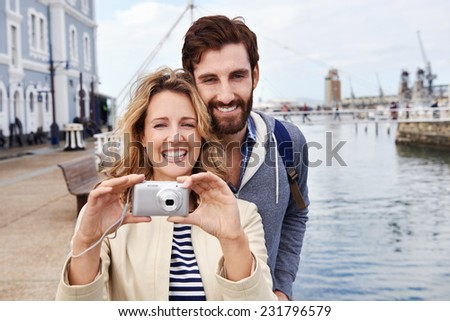 young couple taking photos on holiday as they travel together - stock photo