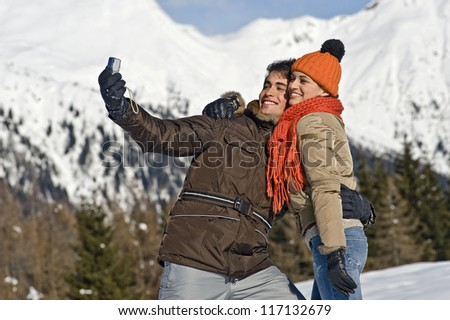 Young couple taking photos on the snow