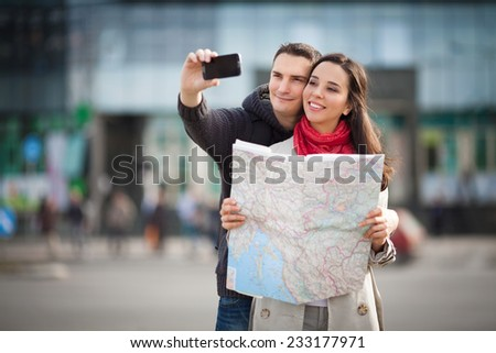 Young couple taking self portrait on the street - stock photo