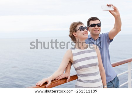 young couple taking selfie with smartphone while cruising, vacation concept - stock photo