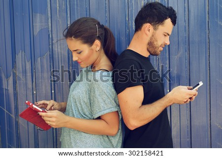 Young couple taking using smartphones. Selfie, social networks, internet addiction, love, friendship, young adult, leisure concept. Image toned and noise added. - stock photo