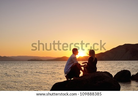 Young couple talking on a rock by the sea at the setting sun - stock photo