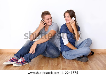 Young couple talking on mobile phone - stock photo