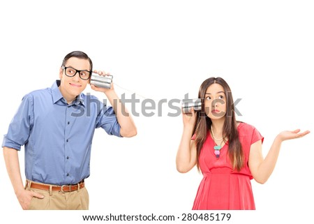 Young couple talking through a tin can phone. The woman is gesturing confusion and the man is smiling and listening carefully isolated on white background - stock photo