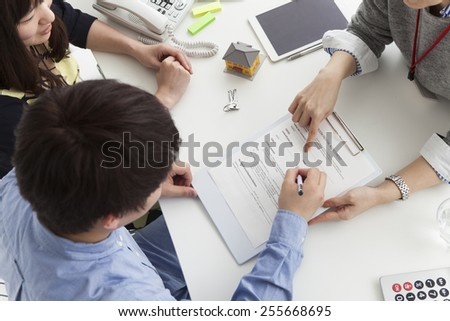 Young couple talking to real estate agent - stock photo