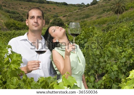 young couple tasting wine in a vineyard