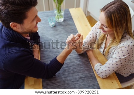 Young couple testing their strengths sitting at a table doing arm wrestling with happy smiles, high angle view - stock photo