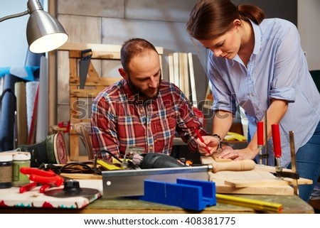 Young couple tinkering in home workshop, busy. - stock photo