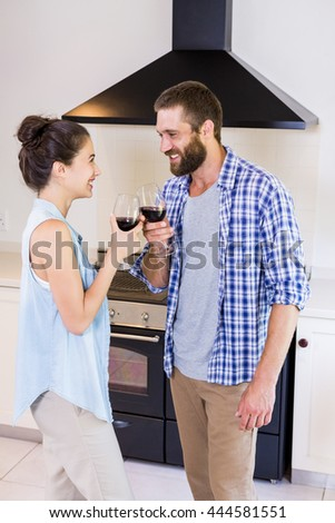 Young couple toasting wine glass in kitchen at home - stock photo