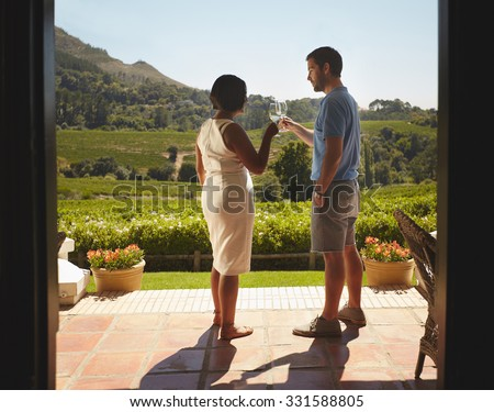 Young couple toasting wine while standing outdoors at winery restaurant patio. Man and woman on vacation celebrating with wine. - stock photo