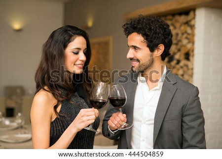 Young couple toasting wineglasses in a luxury restaurant - stock photo