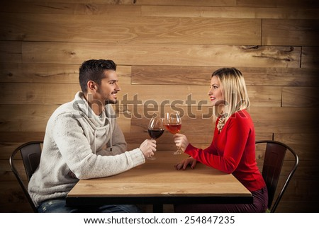 Young couple toasting with wine in a restaurant - stock photo