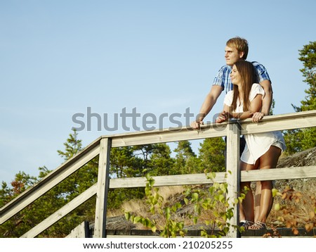Young couple together on the fence, rocky and wooden environment