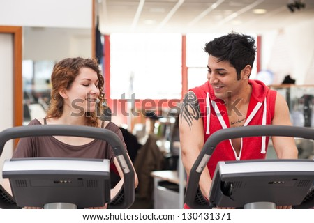 Young couple training in the gym with bike while talking together.