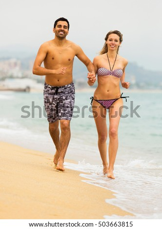 Young couple training on the sea waves and smiling