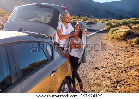 Young couple travelers in white t-shirts and gray hats embracing near the car on the road. - stock photo