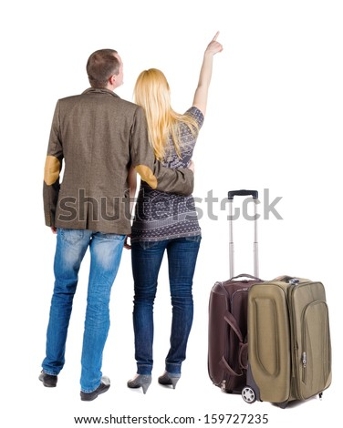young couple traveling with suitcas and pointing at wal Back view. Rear view people collection.  backside view of person.  Isolated over white background. - stock photo