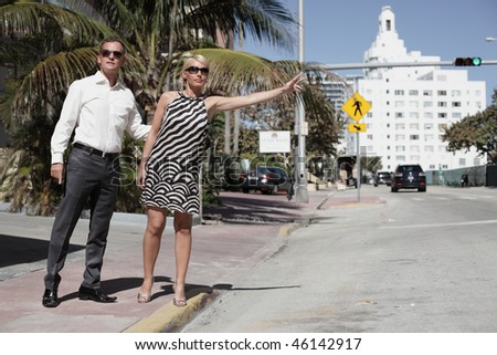 Young couple trying to hail a cab on the street - stock photo