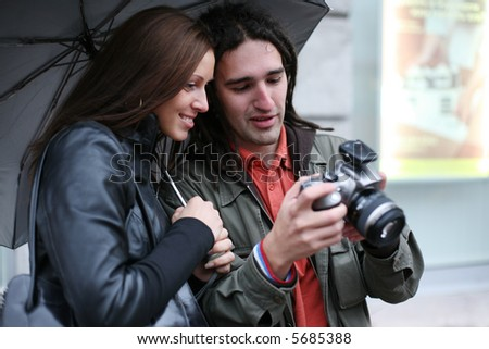 Young couple under umbrella, looking at digital SLR camera, smiling. Selective focus. - stock photo
