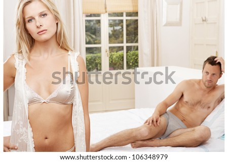 Young couple unhappy in a bedroom. - stock photo