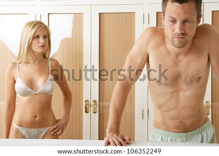Young couple unhappy with their relationship, standing by bedroom's wardrobe. - stock photo