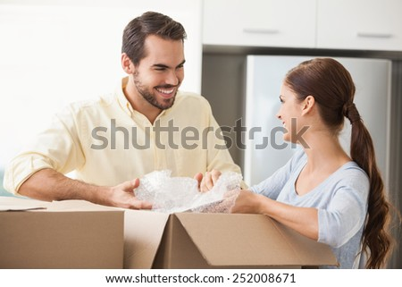Young couple unpacking boxes in kitchen in their new home - stock photo