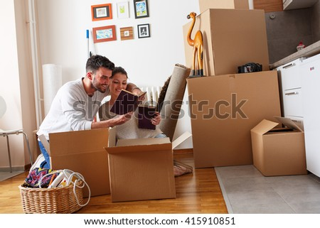 Young couple unpacking cardboard boxes at new home.Moving house.Reading a old books. - stock photo
