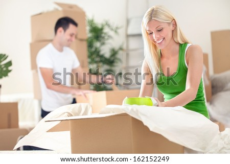 young couple unpacking moving boxes in a living room - stock photo