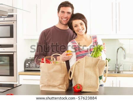Young Couple Unpacking Shopping In Modern Kitchen - stock photo