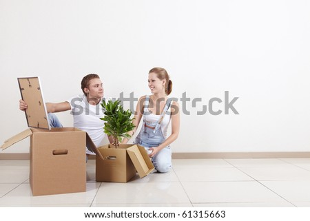Young couple unpacks boxes when moving