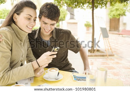 Young couple using a cell phone and writing postcards in a coffee shop while on vacations. - stock photo