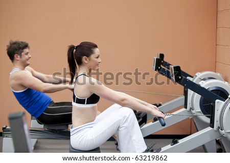 Young couple using a rower in a sport centre