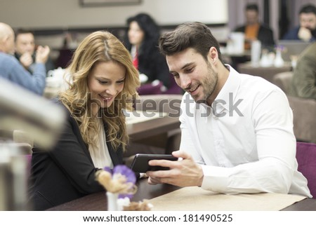 Young couple using a smartphone in hotel restaurant  - stock photo
