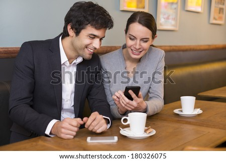 Young couple using a smartphone in restaurant - stock photo