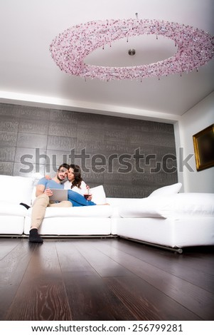 Young couple using a Tablet PC together on the Sofa at home.  - stock photo